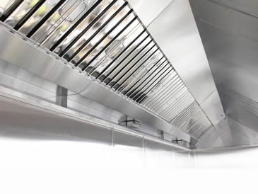 Several stainless steel baffle grease filters with fold flat handles are installed at commercial kitchen