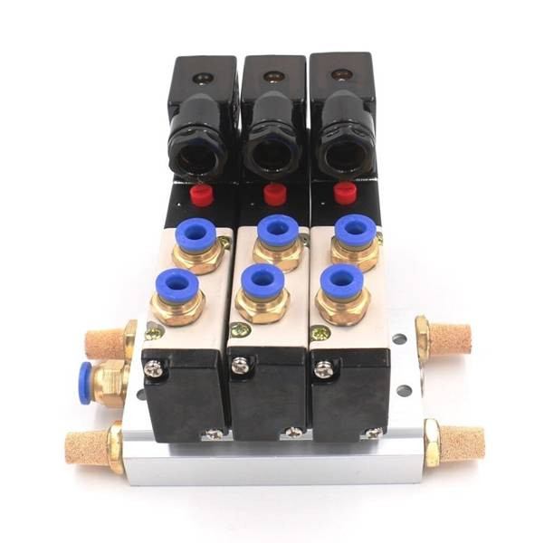 Brass silencers are inserted into a pneumatic triple solenoid valve.